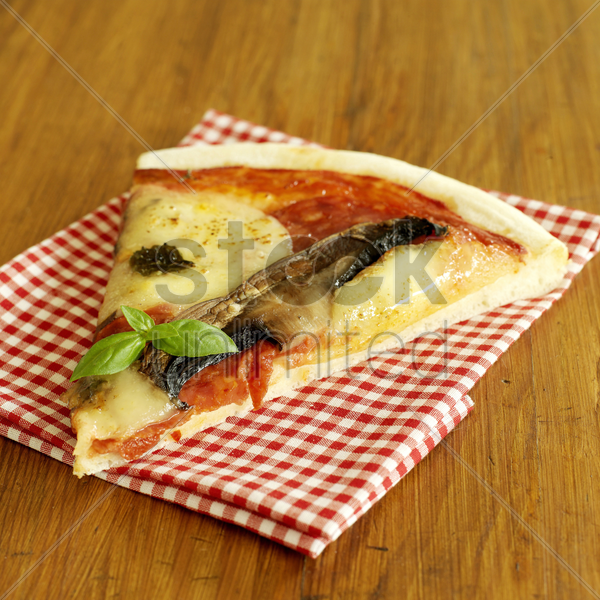 slice of cooked pizza on gingham red napkin stock photo