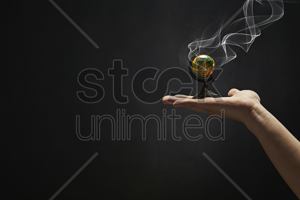 small globe placed on human hand stock photo