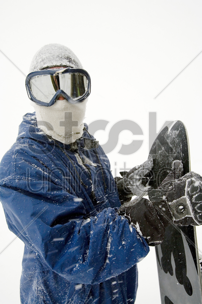 snowboarder posing with snowboard stock photo