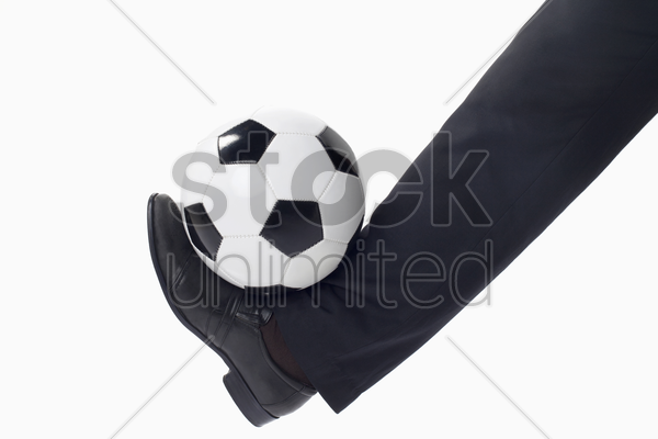soccer manager balancing a ball with leg stock photo