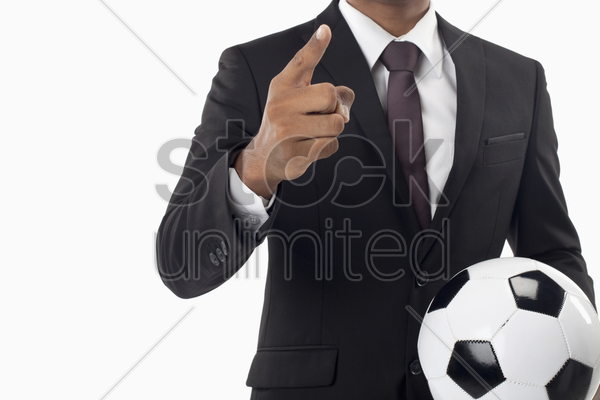 soccer manager holding a ball and pointing stock photo