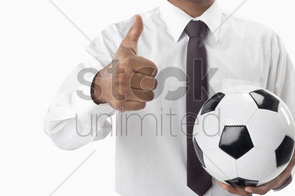 soccer manager holding a ball and thumbs up stock photo