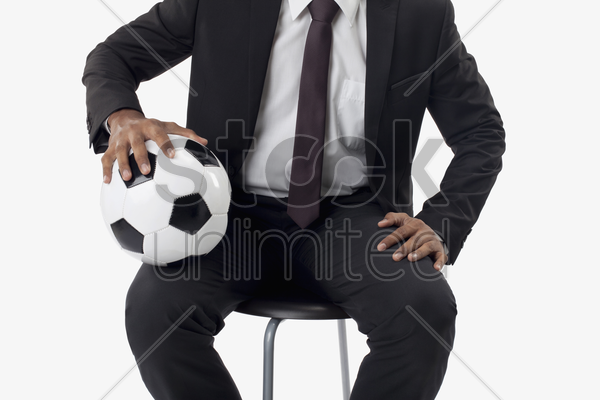 soccer manager holding a ball on his lap stock photo