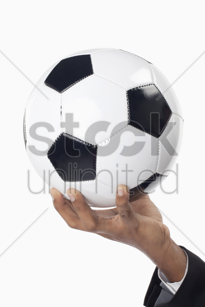 soccer manager holding a ball with one hand stock photo