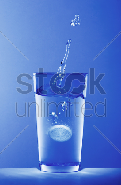 soluble pill dropping into a glass of water stock photo