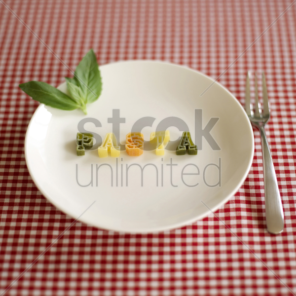 some alphabet pasta being arranged into a word stock photo