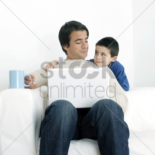 son watching father using laptop stock photo