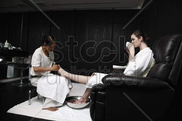 spa attendant massaging a woman's foot stock photo