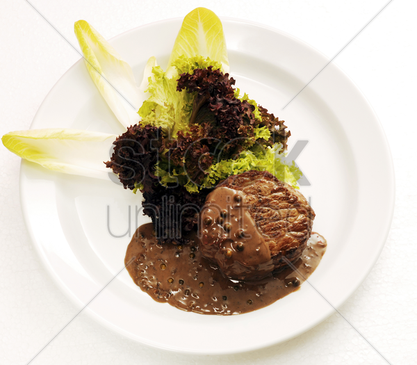 steak fillet with peppercorn sauce and rocket salad stock photo
