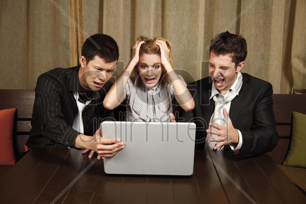 stressed business people looking at laptop stock photo