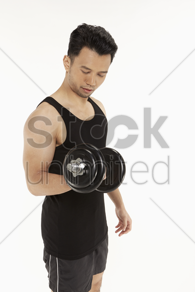 strong man lifting dumbbells stock photo