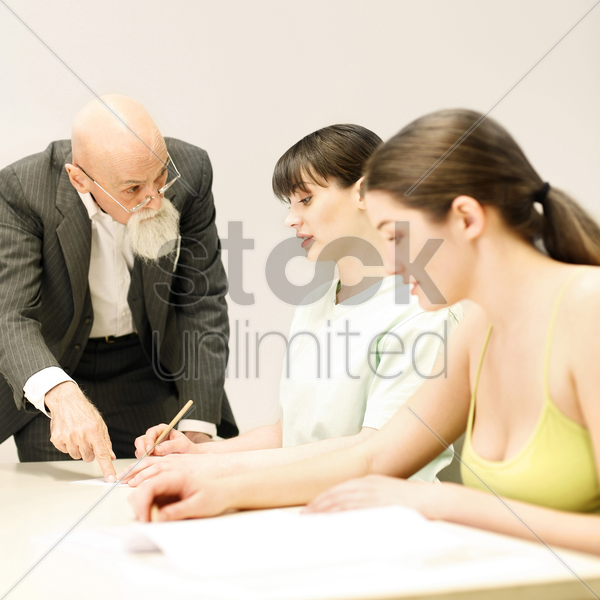 students getting advice from their lecturer stock photo