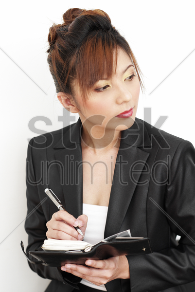 studio shot of a lady in office attire writing on her organizer stock photo