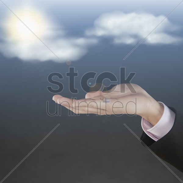 sun and clouds floating above human hand stock photo