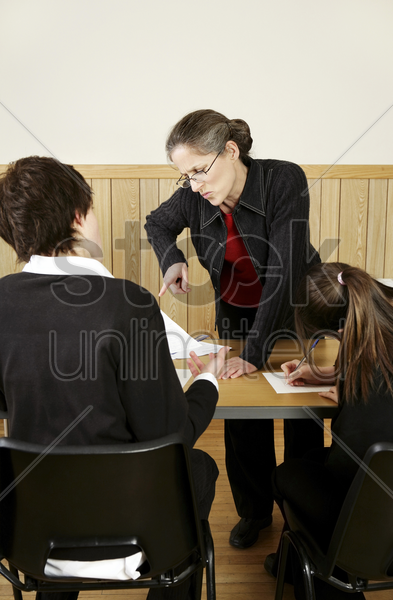 teacher scolding her student for not completing his homework stock photo