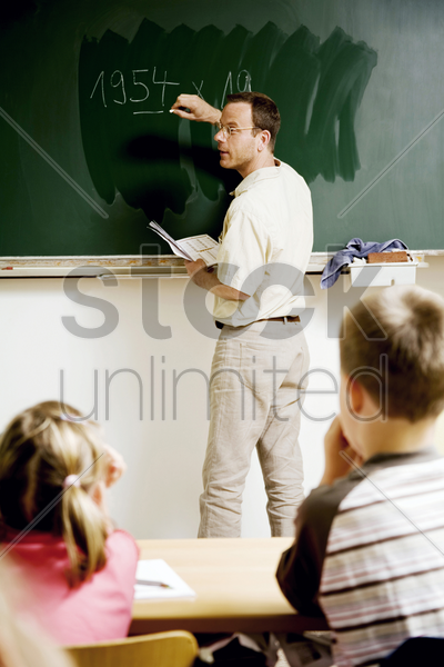 teacher writing on the blackboard with children paying attention stock photo
