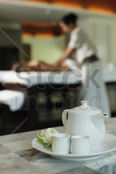 teapot and tea cups, woman receiving massage on the background stock photo
