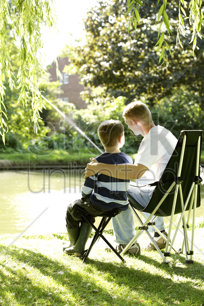 teenage boy and his brother fishing by the lake side stock photo