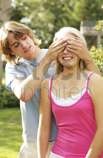 teenage boy covering his girlfriend's eyes stock photo
