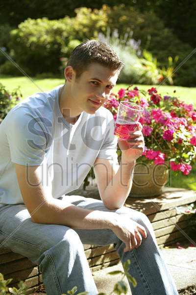 teenage boy drinking in the park stock photo