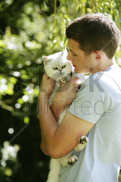 teenage boy hugging his pet cat stock photo