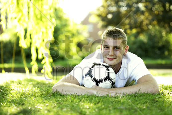 teenage boy lying forward on the field hugging a soccer ball stock photo
