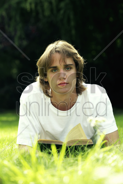 teenage boy lying forward on the field reading book stock photo