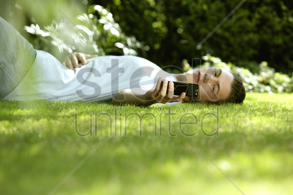 teenage boy lying on the field taking his own picture with camera phone stock photo