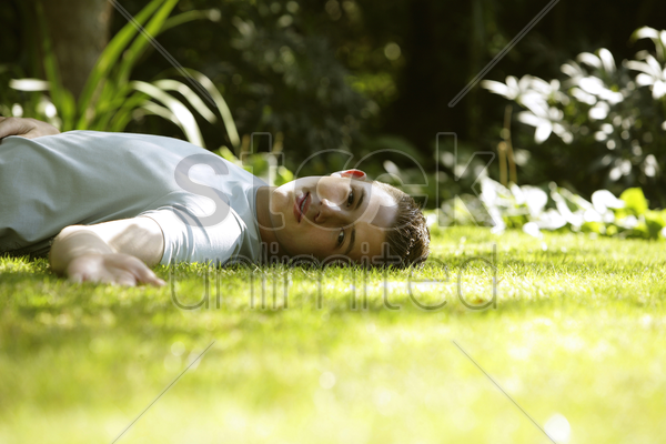 teenage boy lying on the field stock photo