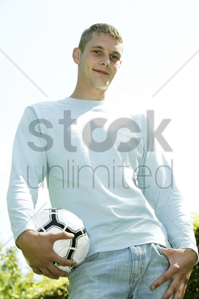 teenage boy posing with a soccer ball on the field stock photo