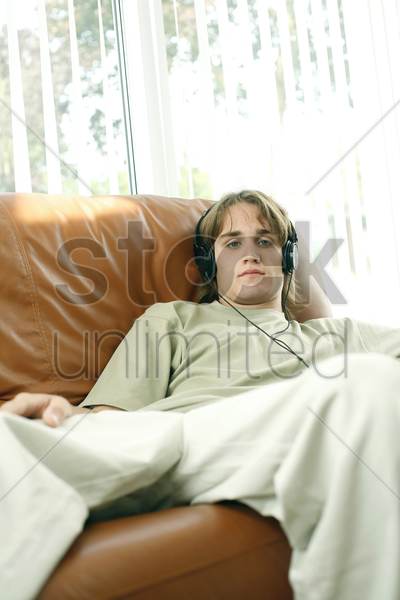 teenage boy sitting on the couch listening to music on the headphones stock photo