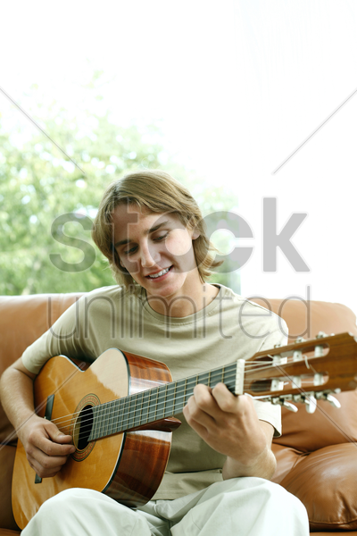 teenage boy sitting on the couch playing guitar stock photo