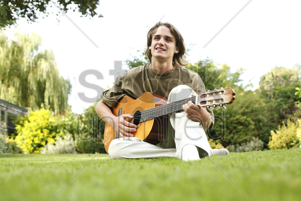 teenage boy sitting on the field playing guitar stock photo