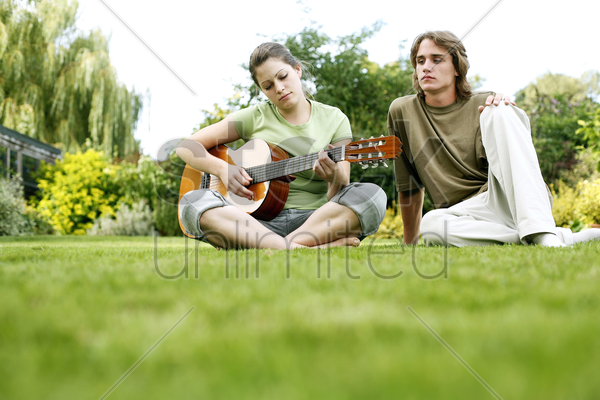teenage boy watching his girlfriend playing guitar stock photo