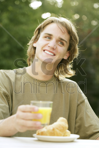 teenage boy with a glass of orange juice and a plate of croissants stock photo