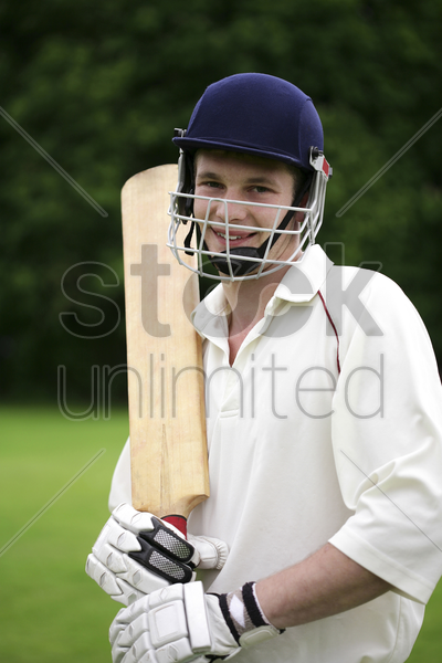 teenage boy with sports helmet and cricket bat posing for the camera stock photo