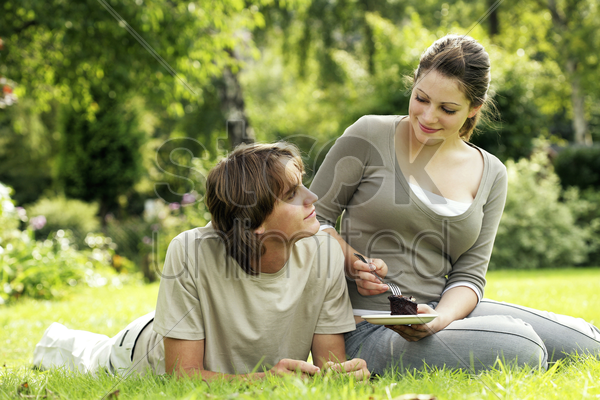 teenage couple enjoying a piece of cake on the field stock photo