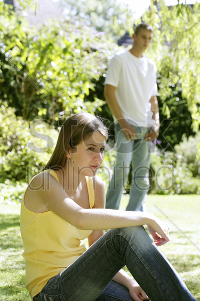teenage couple hanging out in the park stock photo