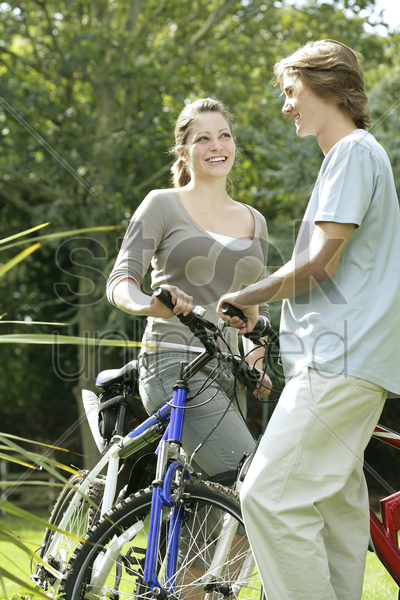 teenage couple with their bicycles stock photo