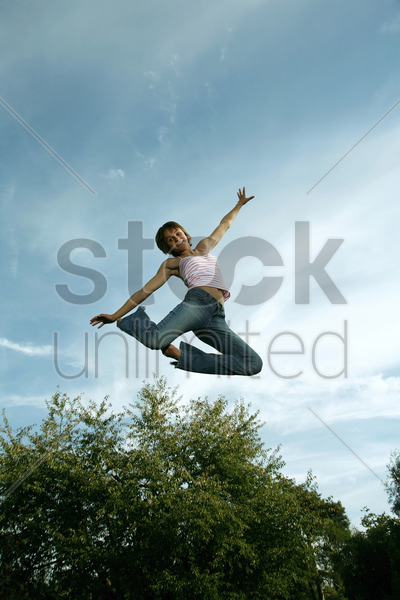 teenage girl jumping with joy stock photo
