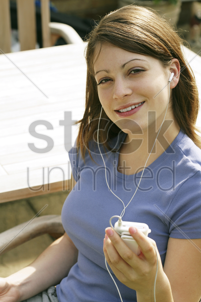 teenage girl listening to music on a portable mp3 player stock photo