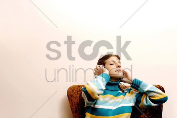 teenage girl listening to music on the headphones stock photo