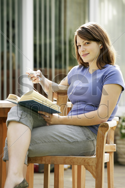 teenage girl listening to music while reading book stock photo