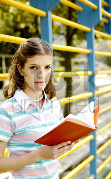 teenage girl looking at the camera while holding a book stock photo
