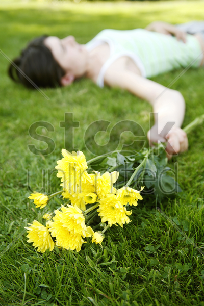 teenage girl lying down on the field with yellow flowers in her hand stock photo