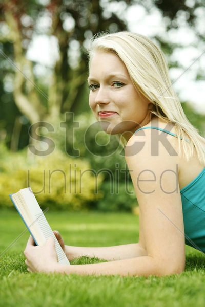 teenage girl lying forward on the field holding book stock photo