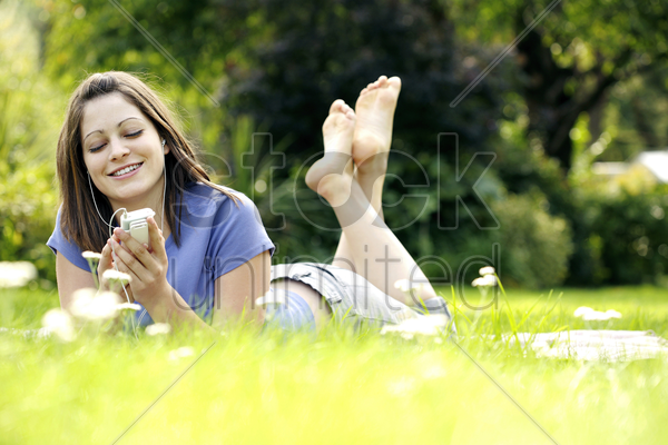 teenage girl lying forward on the field listening to music on a portable mp3 player stock photo