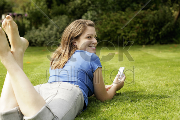 teenage girl lying forward on the field playing with her mobile phone stock photo