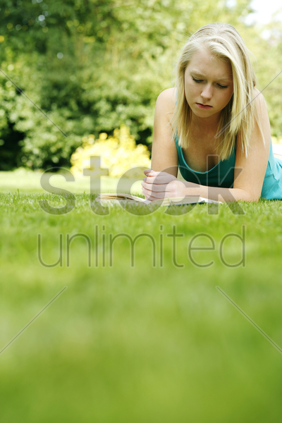 teenage girl lying forward on the field reading book stock photo