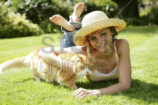teenage girl lying forward on the field with her cat stock photo